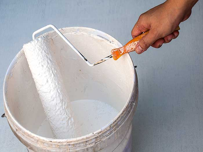 dipping paint roller into paint