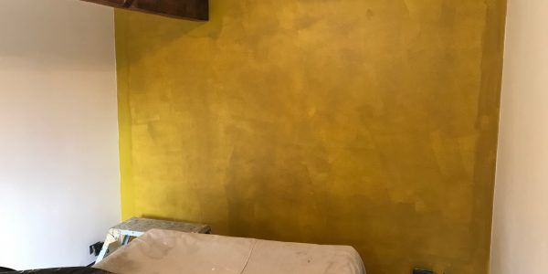 mustard wall with brown wooden beam