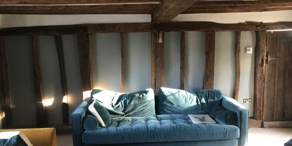 blue sofa with wooden beams on ceiling